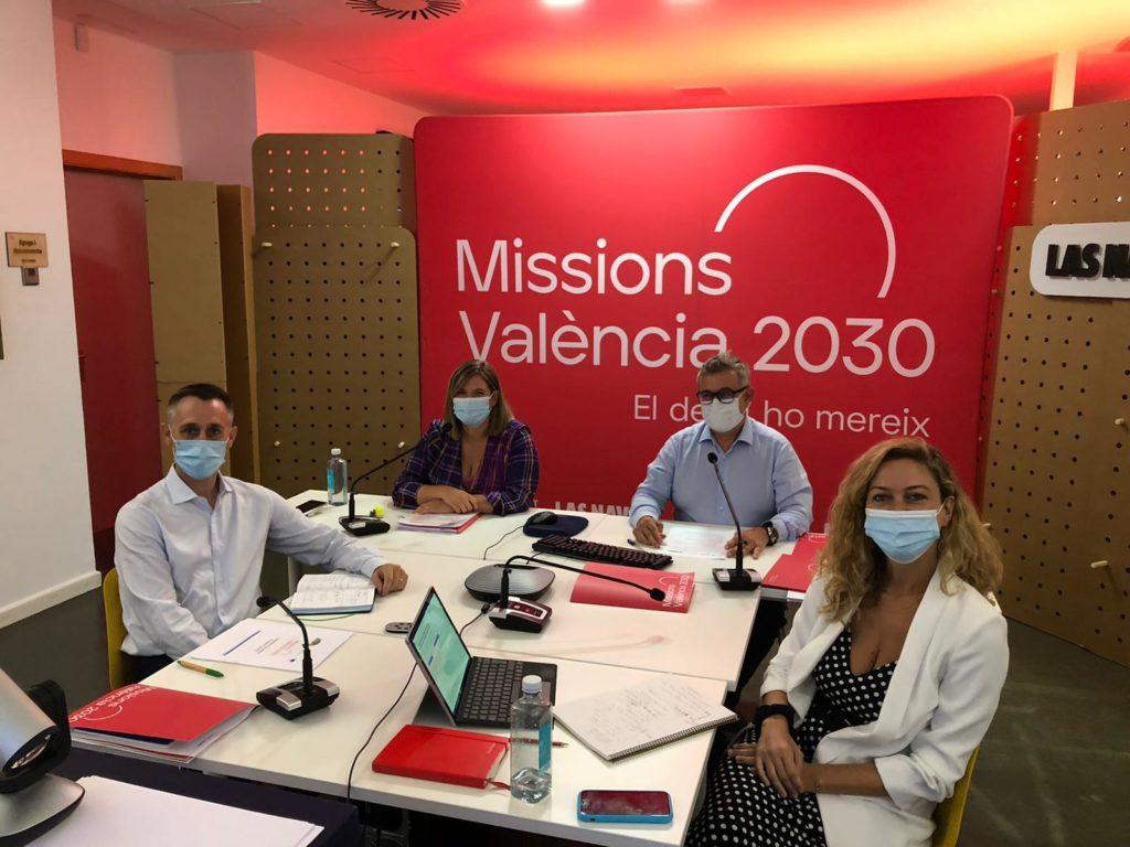 reunión de personas con el logo de Missionas València 2030 detrás